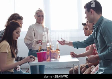 les jeunes amis jouant au jeu de nom tout en étant assis à la table avec des boissons et des jetons Banque D'Images