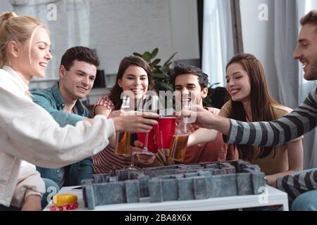 KIEV, UKRAINE - 27 JANVIER 2020: Des amis heureux s'inclinent avec de la bière et du vin au-dessus du jeu de plateau de labyrinthe Banque D'Images