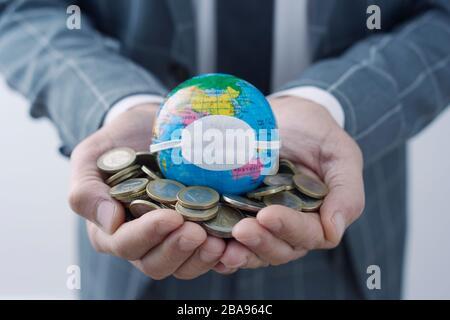 homme d'affaires tenant un globe mondial avec un masque protecteur sur une poignée de pièces en euros, représentant les conséquences économiques du pan du coronavirus Banque D'Images