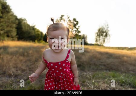 Petite fille joue dans la nature. Les filles de bébé s'amusent dans le parc, courir pieds nus sur l'herbe verte. Enfance amusante et insouciante. Banque D'Images