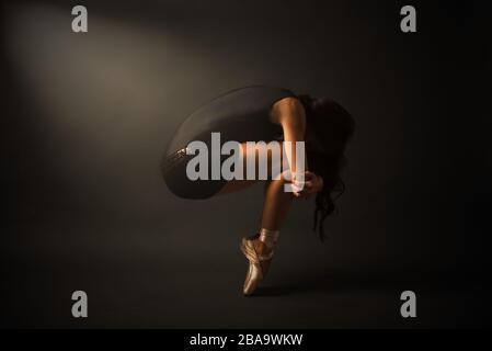 Danseur. Jeune danseuse de ballet élégante, vêtue de jersey noir, chaussures et Banque D'Images