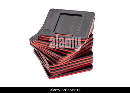 Gros plan d'une pile de lames de film 35 mm à cadre noir rouge, isolées sur fond blanc. Divertissement du siècle dernier pour regarder des photos de vacances sur un proj Banque D'Images
