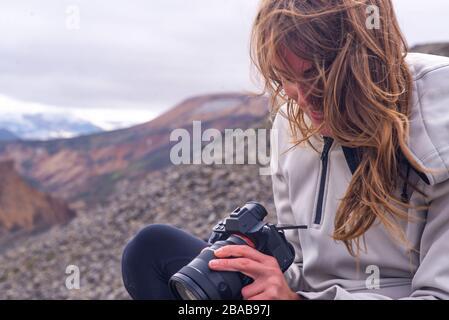 Femme assis regardant la caméra dans le vent, à Landmannalaugar
