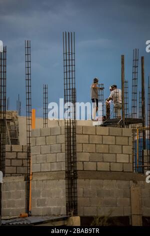 Deux ouvriers du bâtiment travaillent ou sur le toit, soudant des rails métalliques.