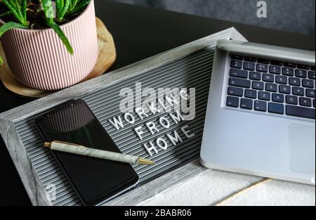 Tableau de composition avec texte « TRAVAILLER À DOMICILE », smartphone, ordinateur portable et stylo sur le bureau. Travailler à domicile pendant le concept de quarantaine, Covid-19.