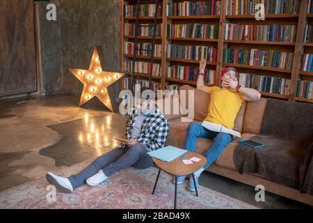 Deux jeunes hommes qui étudient avant les examens et se sentent fatigués Banque D'Images