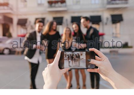 Femme avec peau pâle et manucure noire faisant photo d'amis pendant le voyage dans le pays. Portrait extérieur des jeunes debout dans la rue et des mains féminines tenant le smartphone au premier plan. Banque D'Images