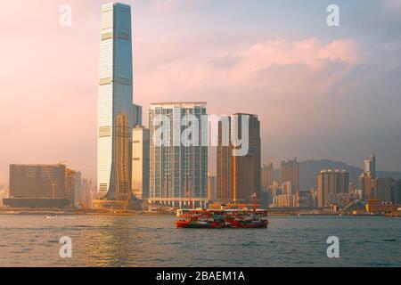 Centre, Hong Kong - 1 mars 2020: Ferry et gratte-ciel étoiles avec le coucher du soleil dans le port de Victoria