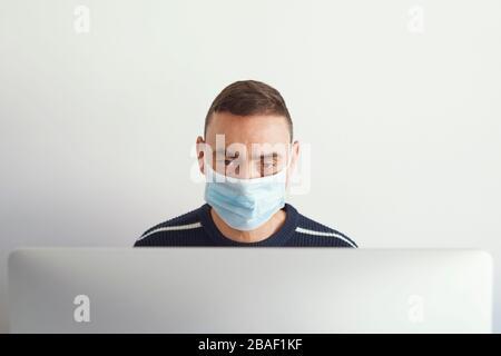 gros plan d'un jeune homme caucasien à l'intérieur, portant un masque chirurgical, à l'aide d'un ordinateur Banque D'Images