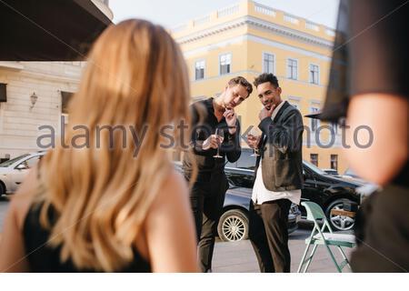 Deux gars en tenue élégante regarde soigneusement blonde fille, touchant chins. Portrait en plein air de l'arrière d'une dame aux cheveux justes qui descend la rue jusqu'à ses amis masculins avec des verres de vin. Banque D'Images
