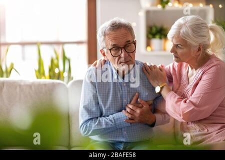 Femme senior consolant son mari à la maison Banque D'Images