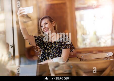 Esquisse de designer féminine avec tablette numérique et stylet au café