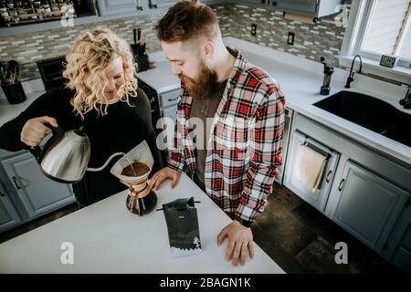 homme et femme se tiennent ensemble dans la cuisine pour faire du café