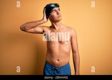 Un jeune homme sans chirless portant un maillot de bain et un bonnet de bain sur fond jaune isolé confondent et se interroge sur la question. Incertain avec doute, Banque D'Images