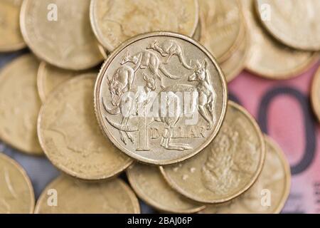 Une pièce australienne d'un dollar untop d'une pile de pièces et de billets de banque. Banque D'Images