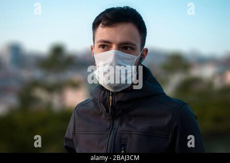 Un jeune homme isolé portant un masque pour se protéger du virus corona regarde vers des bâtiments flous en arrière-plan Banque D'Images