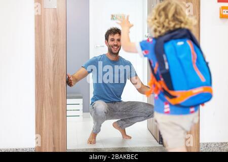 Petit garçon qui court vers son père l'attendait chez lui