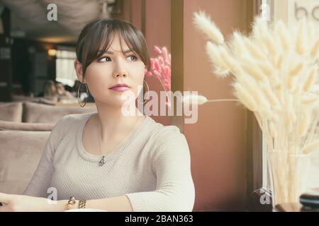 Une jolie femme asiatique attend quelqu'un dans un café Banque D'Images