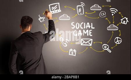 Homme d'affaires qui dessine des icônes de médias sociaux avec inscription DE JEU SOCIAL, concept de nouveaux médias