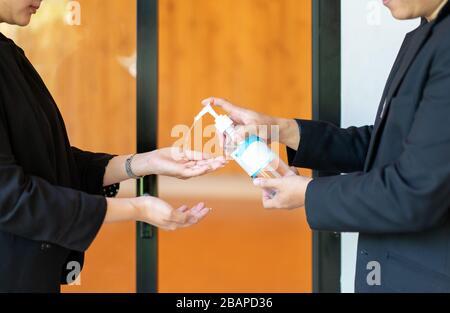 Deux hommes d'affaires et femmes asiatiques en costume noir se lavent les mains par gel d'alcool avant d'entrer dans la salle de séminaire. Banque D'Images