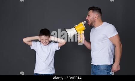 Père nerveux hurlant au fils avec le mégaphone Banque D'Images