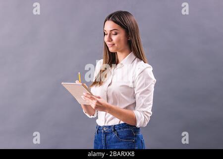 Jeune femme créative prenant des notes dans son carnet et souriant tout en restant isolée sur fond gris. Belle fille écriture ou dessin croquis i