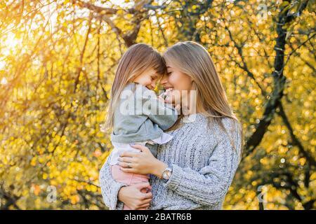 Portrait d'une belle femme affectueuse tenant sa petite fille dans les mains et souriant tout en se tenant dehors. La jeune mère et sa fille embrassent chaque t