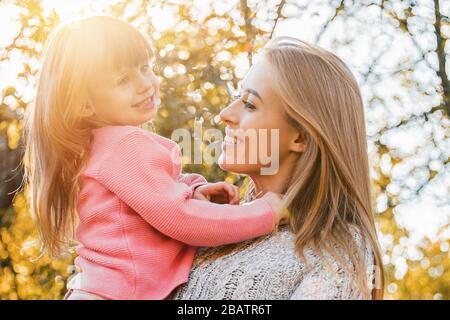 Bonne famille embrassant dans le parc d'automne. Heureuse jeune mère embrassant sa belle petite fille tout en se tenant à l'extérieur. Gai femme tenant
