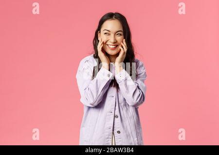 Portrait de sly et créatif jolie petite amie asiatique ont quelque chose sur son esprit, rire comme scheming mauvais plan, regarder de côté touchant les joues et Banque D'Images
