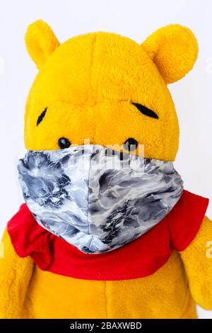 Un ours en peluche jaune avec un masque de protection fait main sur fond blanc se rapproche. Un masque fait à la maison parce qu'il y a un manque d'équipement de protection Banque D'Images