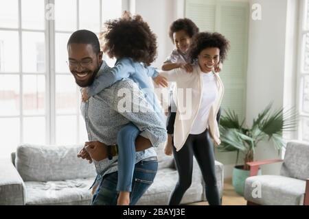 Un couple africain joyeux joue avec de petits enfants à la maison Banque D'Images