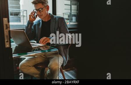 Homme d'affaires parlant sur téléphone mobile et regardant son ordinateur portable. Homme assis à son bureau travaillant sur un ordinateur portable et discutant au téléphone.