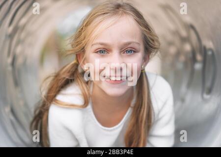 Jolie petite fille, amusante, posée sur un tuyau sur une aire de jeux pour enfants. Banque D'Images