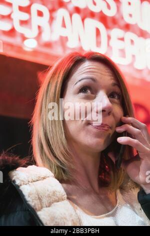 Jeune blonde jolie femme parlant au téléphone dans le centre-ville la nuit. Néons rouges à l'arrière-plan.