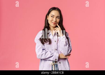 HMM intéressant. Portrait d'une jeune fille créative souriante dans une veste denim, pensant, ont une idée fascinante, smirk et regarder le coin supérieur gauche, rêvant de jour Banque D'Images