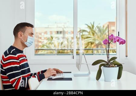 gros plan d'un jeune homme caucasien à l'intérieur, portant un masque chirurgical, à l'aide d'un ordinateur assis sur une table blanche Banque D'Images