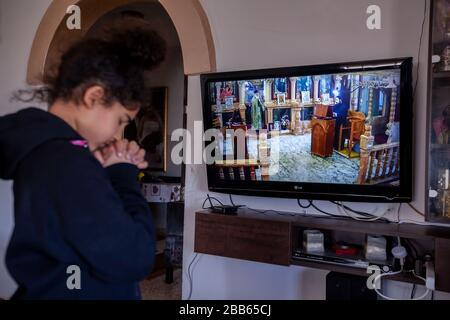 (200330) -- BETHLÉEM, le 30 mars 2020 (Xinhua) -- une jeune fille palestinienne prie alors qu'elle regarde une émission télévisée en direct de la messe du dimanche d'une église orthodoxe à Beit Sahour près de la ville de Bethléem, en Cisjordanie, le 29 mars 2020. Pour la première fois, Raed al-Atrash, un palestinien de 54 ans de la ville de Bethléem, en Cisjordanie, a assisté à la messe du dimanche avec sa famille par une émission télévisée en direct, puisque les églises sont fermées dans le cadre des précautions contre la propagation du roman coronavirus.TO GO WITH 'Feature: Les chrétiens de Palestine assistent à des prières en direct lorsque des églises se ferment sur le fea de coronavirus Banque D'Images