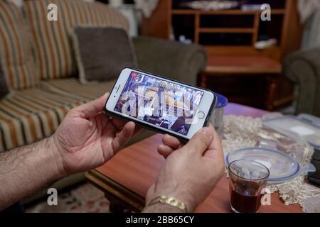 (200330) -- BETHLÉEM, le 30 mars 2020 (Xinhua) -- un palestinien regarde une diffusion Internet de la messe du dimanche d'une église orthodoxe à Beit Sahour près de la ville de Bethléem, en Cisjordanie, le 29 mars 2020. Pour la première fois, Raed al-Atrash, un palestinien de 54 ans de la ville de Bethléem, en Cisjordanie, a assisté à la messe du dimanche avec sa famille par une émission télévisée en direct, puisque les églises sont fermées dans le cadre des précautions contre la propagation du roman coronavirus.TO GO WITH 'Feature: Les chrétiens de Palestine assistent à des prières en direct lorsque les églises se ferment sur les peurs du coronavirus (photo de lu Banque D'Images