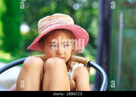 Portrait de la petite fille triste mignonne à grand chapeau regardant triste le jour d'été