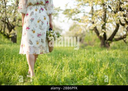Une fille marche dans un parc vert printemps profiter de la nature en fleurs.