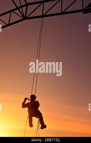 Silhouette d'un travailleur de la construction accroché au harnais de sécurité sur un chantier de construction, Thaïlande