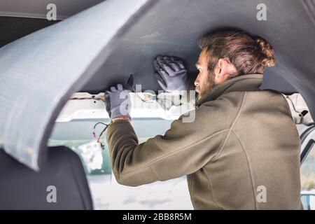 Homme travaillant sur l'isolation à l'intérieur de son camping-car Banque D'Images