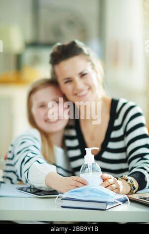 Gros plan sur la jeune mère et l'enfant heureux dans les chandails à rayures dans le bureau à domicile temporaire à la maison moderne en journée ensoleillée montrant des mains désinfectantes.