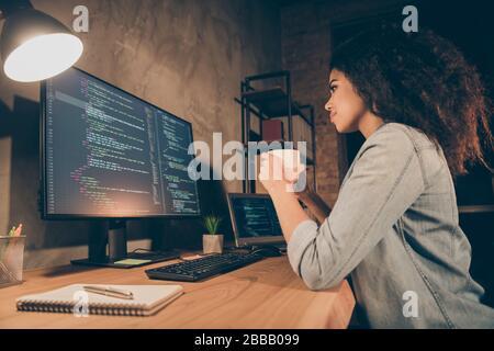 Profil côté photo focalisé habile afro american girl développeur logiciel assis soir table de bureau boire espresso look ordinateur écran données de travail