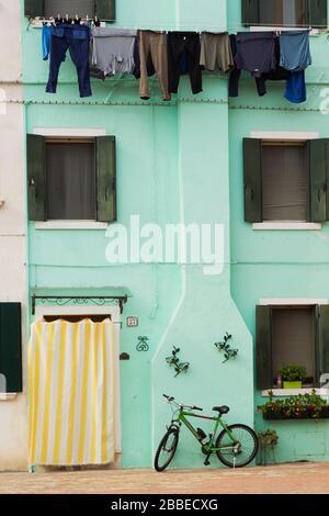 Façade de maison en stuc vert décorée avec un rideau à rayures blanches et jaunes sur la porte d'entrée et des vêtements lavés sur le clothesline, la bicyclette, l'île de Burano, la lagune vénitienne, Venise, Vénétie, Italie Banque D'Images