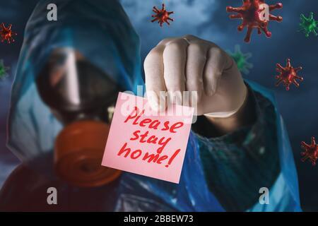Un homme dans un masque à gaz contient une note avec du texte. Concept sur la nécessité de rester à la maison en raison de la pandémie covid-19 Banque D'Images