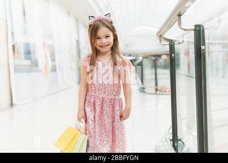 Portrait d'une petite fille heureuse dans le centre commercial. Une jeune fille souriante en riant dans une robe rose avec un joli bord avec des oreilles et avec des sacs multicolores dans ses mains est de marcher autour du centre commercial, en regardant l'appareil photo.