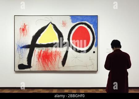 """Visiteur devant la peinture du peintre moderniste espagnol Joan Miró intitulée """"Figure devant le soleil"""" (1968) exposé dans la Fundació Joan Miró (Fondation Joan Miró) à Barcelone, Catalogne, Espagne. Banque D'Images"""