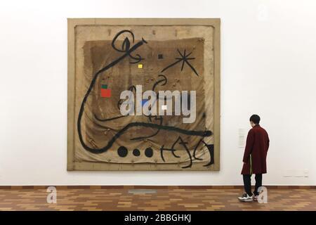 Visiteur devant la peinture par le peintre moderniste espagnol Joan Miró intitulée 'Femme encerclée par un vol d'oiseau dans la nuit' (1968) affichée dans la Fundació Joan Miró (Fondation Joan Miró) à Barcelone, Catalogne, Espagne. L'œuvre est peinte sur le robinet utilisé pour transporter les raisins pendant la récolte. Banque D'Images