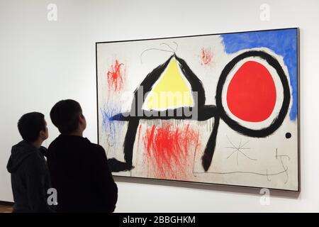"""Visiteurs devant la peinture du peintre moderniste espagnol Joan Miró intitulée """"Figure devant le soleil"""" (1968) présentée dans la Fundació Joan Miró (Fondation Joan Miró) à Barcelone, Catalogne, Espagne. Banque D'Images"""